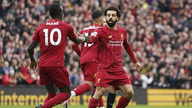 Liverpool's Mohamed Salah, right, celebrates with his teammate Sadio Mane after scoring his side's opening goal during the English Premier League soccer match between Liverpool and Bournemouth at Anfield stadium in Liverpool, England, Saturday, March 7, 2020. (AP Photo/Jon Super)