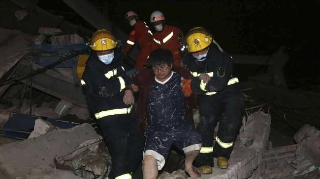 Tim penyelamat membantu pria keluar dari reruntuhan hotel di Quanzhou, China. Hotel yang digunakan sebagai tempat karantina virus corona tersebut ambruk Sabtu (7/3). (Chinatopix via AP).