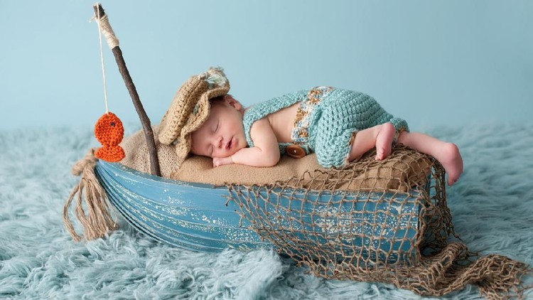 Portrait of a three week old newborn baby boy. He is sleeping in a miniature boat and wearing crocheted overalls and a fisherman's hat. Shot in the studio on an aqua colored flokati rug.