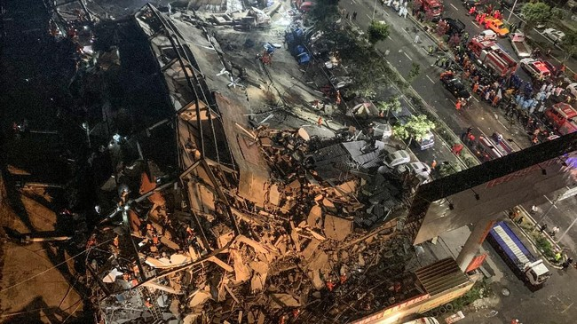 Tim penyelamat mencari korban selamat dari reruntuhan puing hotel di Quanzhou, China yang digunakan sebagai tempat karantina virus corona. Hotel ambruk pada Sabtu (7/3). (Photo by STR / AFP) / China OUT.