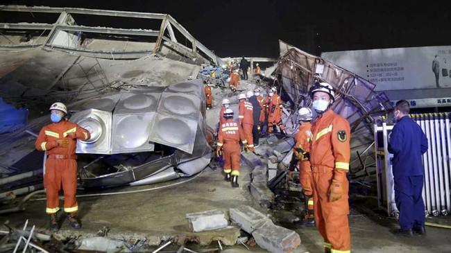Tim penyelamat mencari korban reruntuhan hotel berlantai lima di Quanzhou, China. Hotel digunakan sebagai tempat karantina virus corona tersebut ambruk Sabtu (7/3) dan menjebak puluhan orang. (Chinatopix Via AP).