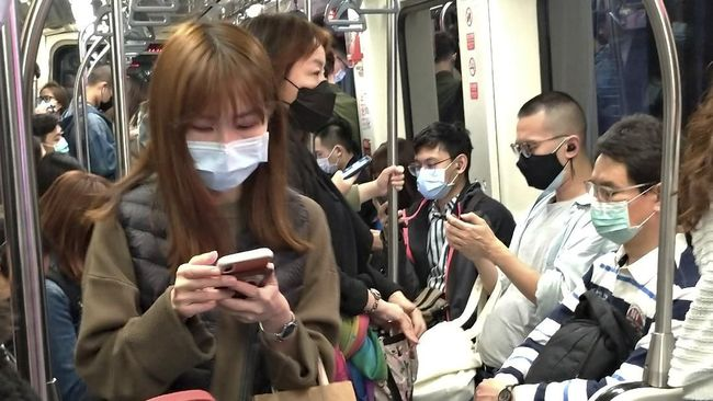 People wear face masks to protect against the spread of the coronavirus on MRT in Taipei, Taiwan, Saturday, March 7, 2020. (AP Photo/Chiang Ying-ying)