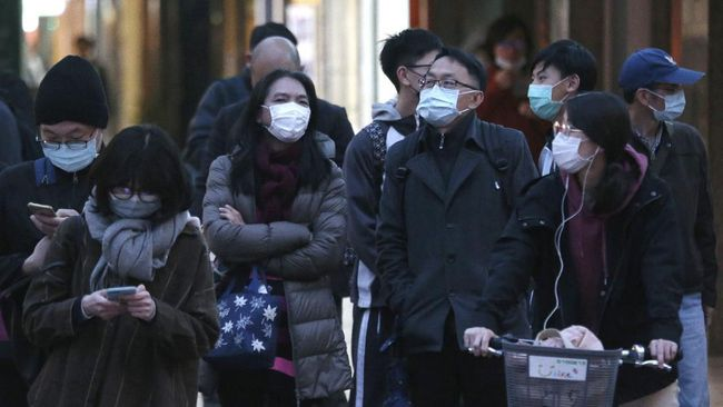 People wearing face masks as a precaution against the new coronavirus stand on a street in Taipei, Taiwan, Thursday, March 5, 2020. (AP Photo/Chiang Ying-ying)
