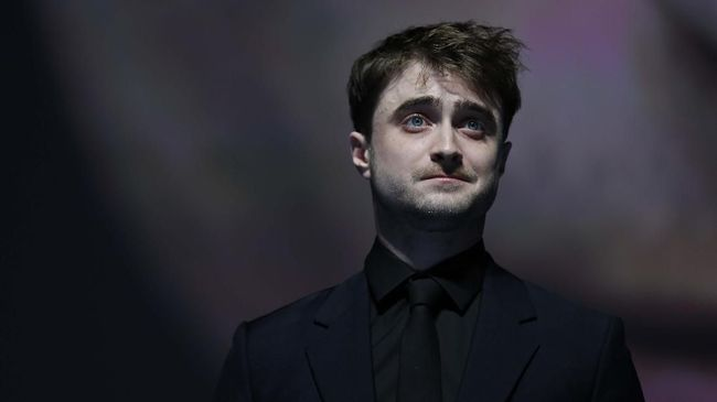 Actor Daniel Radcliffe reacts on stage after receiving the