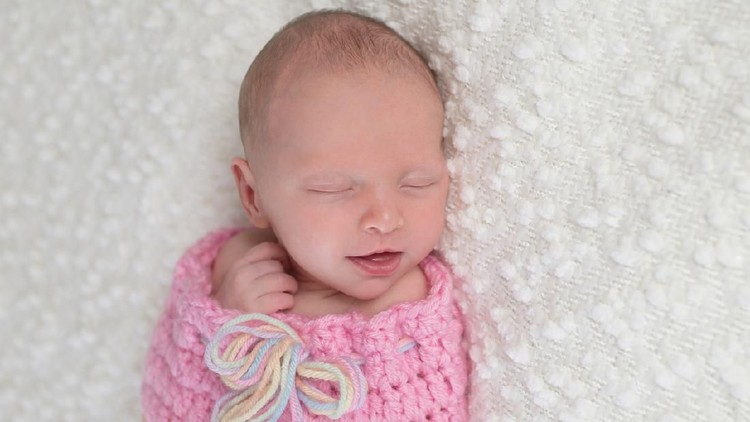 Headshot of a smiling three week old newborn baby girl bundled up in a light pink, crocheted, snuugle sack. She is lying on a white, bouncle blanket.