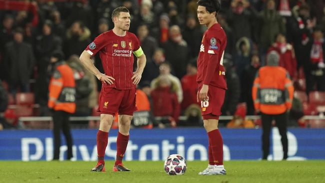 Liverpool's James Milner, left, and Liverpool's Takumi Minamino stand in dejection after Atletico Madrid's Alvaro Morata scores his side's third goal during a second leg, round of 16, Champions League soccer match between Liverpool and Atletico Madrid at Anfield stadium in Liverpool, England, Wednesday, March 11, 2020. (AP Photo/Jon Super)