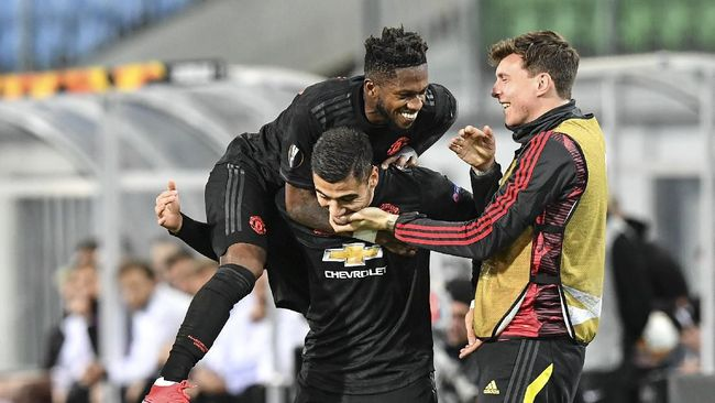 Manchester United's Fred jumps on Manchester United's scorer Andreas Pereira who scored his side's 5th goal during the Europa League round of 16 first leg soccer match between Linzer ASK and Manchester United in Linz, Austria, Thursday, March 12, 2020. The match is being played in an empty stadium because of the coronavirus outbreak. (AP Photo/Kerstin Joensson)