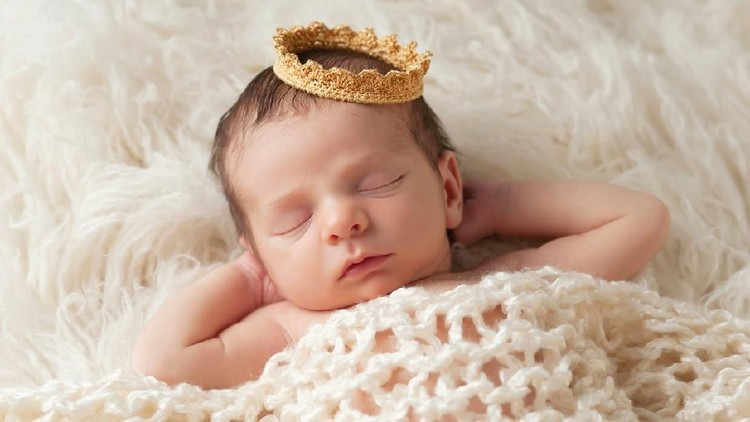 Portrait of a 12 day old newborn baby boy wearing a gold crown. He is sleeping on a beige flokati rug with his hands behind his head.