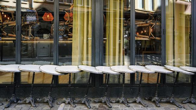 Tables are lined up in front of a closed restaurant in Lyon, central France, Sunday, March 15, 2020. French Prime Minister Edouard Philippe announced that France is shutting down all restaurants, cafes, cinemas and non-essential retail shops, starting Sunday, to combat the accelerated spread of the virus in the country. For most people, the new coronavirus causes only mild or moderate symptoms. For some it can cause more severe illness. (AP Photo/Laurent Cipriani)