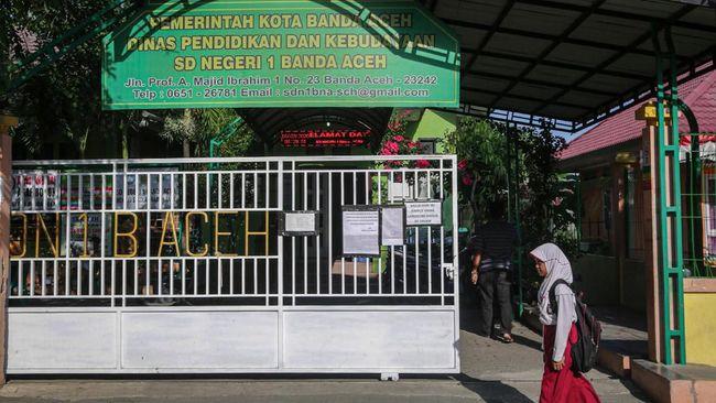 Pelajar keluar dari pekarangan sekolah SD Negeri 1 yang telah diliburkan di Banda Aceh, Aceh, Senin (16/3/2020). Pemerintah Aceh mengeluarkan kebijakan meliburkan sekolah selama dua minggu mulai tanggal 16 hingga 30 Maret 2020 guna antisipasi penyebaran Corona Virus Disease 2019 (COVID-19). ANTARA FOTO/Irwansyah Putra/foc.