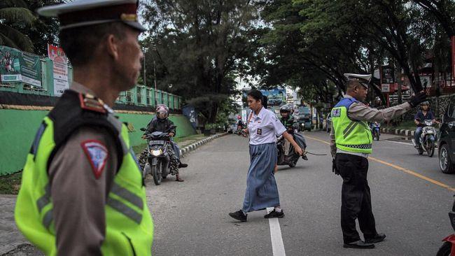 Personel Satuan Lalulintas Polres Kendari membantu menyeberangkan siswa SMA Negeri 4 Kendari untuk melaksanakan ujian sementer hari terakhir sebelum diliburkan, Kendari, Sulawesi Tenggara, Senin (16/3/2020). Pemerintah Kota Kendari menginstruksikan seluruh sekolah meliburkan para siswa Taman Kanak-Kanak, SD, SMP dan SMA terhitung sejak 16 sampai 27 Maret 2020 guna antisipasi penyebaran virus COVID-19. ANTARA FOTO/Jojon/foc.