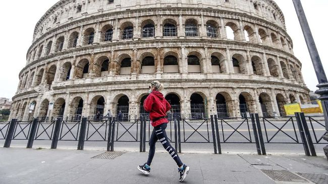 A woman runs by the Colosseum in Rome Friday, March 13, 2020. A sweeping lockdown is in place in Italy to try to slow down the spread of coronavirus epidemic. Among exception to the ordinance to remain home, there is the need for open air fitness. For most people, the new coronavirus causes only mild or moderate symptoms. For some, it can cause more severe illness, especially in older adults and people with existing health problems. (Cecilia Fabiano/LaPresse via AP)