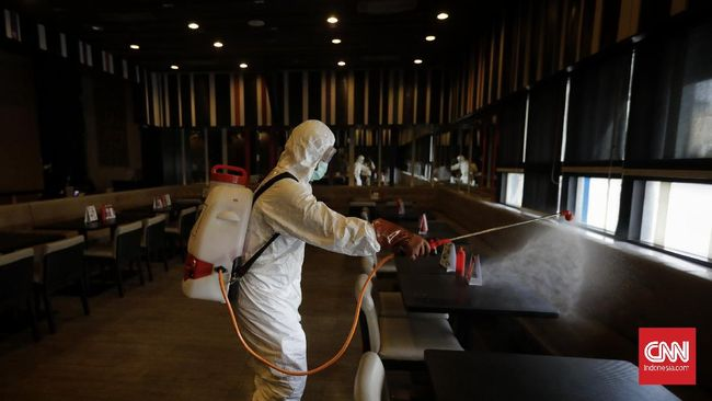 Petugas Palang Merah Indonesia (PMI) melakukan penyemprotan cairan disinfektan di pusat perbelanjaan dan perkantoran Sarinah, Jakarta Pusat, Selasa (17/3/2020). PMI melakukan penyemprotan disinfektan di sejumlah tempat seperti pasar, perkantoran, terminal dan tempat ibadah tersebut untuk mencegah penyebaran virus Corona (COVID-19).  CNN Indonesia/Adhi Wicaksono