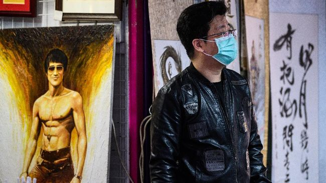 A man wears a facemask while standing next to a painting depicting martial arts icon and film actor Bruce Lee (L) at his art materials and paintings street stall in Hong Kong on February 4, 2020, as a preventative measure following a virus outbreak which began in the Chinese city of Wuhan. - Hong Kong on February 4 became the second place outside mainland China to report the death of a coronavirus patient as officials said they feared local transmissions were increasing in the densely populated city. (Photo by Anthony WALLACE / AFP)