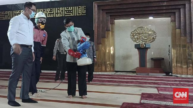 Gubernur Jabar Ridwan Kamil bersama Penceramah Aa Gym menyemprotkan disinfektan di Masjid Al-Mutaqien Provinsi Jabar, Kamis (19/3).