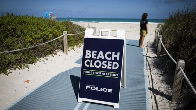A sign details a police order to close the beach in South Beach, Florida, on March 19, 2020. - In response to the virus's spread, Miami Beach and Fort Lauderdale are closing down parts of their public beaches and limit the hours of operations for bars, clubs and restaurants to stifle the spread of coronavirus. (Photo by Eva Marie UZCATEGUI / AFP)