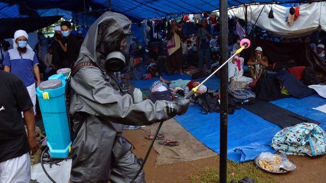 Anggota kepolisian Polda Sulsel menyemprotkan cairan di lokasi kegiatan Ijtima Ulama Asia di Desa Pakkatto, Kecamatan Bontomarannu, Kabupaten Gowa, Sulawesi Selatan, Kamis (19/3/2020). Penyemprotan disinfektan di lokasi tersebut sebagai upaya untuk mencegah penyebaran virus Corona (COVID-19) yang telah mewabah di sejumlah wilayah Indonesia. ANTARA FOTO/Abriawan Abhe/hp.