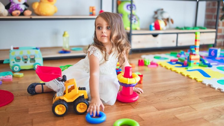 Adorable blonde toddler building pyramid using hoops around lots of toys at kindergarten