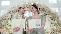 <p>Syamsir dan Bunga tampak bahagia, saling menatap dan menunjukkan buku nikah. (Foto: Instagram @weddingkuconcierge)</p>