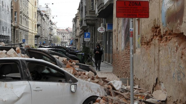 Seorang pria berjalan melewati kendaraan yang rusak tertimpa reruntuhan. Gempa ini membuat warga panik dan berhamburan ke luar rumah dan bangunan. (AP Photo/Darko Bandic)