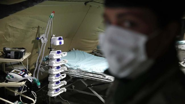 A soldier stands inside the military field hospital built in Mulhouse, eastern France, Monday March 23, 2020. The Grand Est region is now the epicenter of the outbreak in France, which has buried the third most virus victims in Europe, after Italy and Spain. For most people, the new coronavirus causes only mild or moderate symptoms. For some it can cause more severe illness. (AP Photo/Jean-Francois Badias)