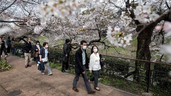 People wearing face masks, amid concerns of the COVID-19 coronavirus, walk under the cherry blossoms in Tokyo on March 22, 2020. (Photo by Behrouz MEHRI / AFP)