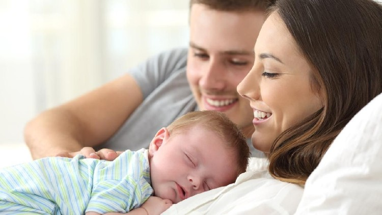 Happy parents watching their baby sleeping on a bed at home