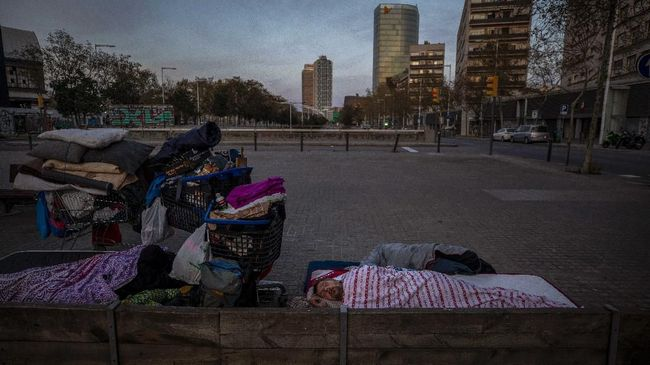 In this Friday, March 20, 2020 photo, Boris, 42, from Bulgaria, sleeps under a blanket in the street in Barcelona, Spain. While Spanish authorities tell the public that staying home is the best way to beat the coronavirus pandemic, some people are staying out because home has come to mean the streets of Madrid and Barcelona. Authorities are scrambling to get as many homeless people off the streets without cramming them into a group shelter, where the risk of getting infected with the virus could be even greater. (AP Photo/Emilio Morenatti)