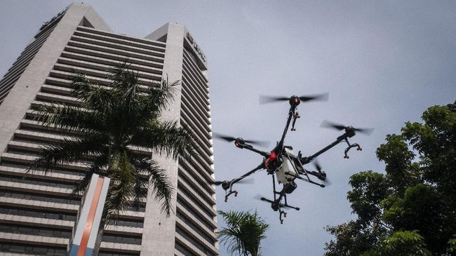Petugas menggunakan drone (pesawat tanpa awak) untuk menyemprotkan cairan disinfektan  di halaman Kantor Pusat BNI, Jakarta, Jumat (20/3/2020). Penyemprotan disinfektan tersebut menjadi salah satu rangkaian program prefentif PT Bank Negara Indonesia (Persero) Tbk (BNI) untuk menekan penyebaran virus Corona (COVID-19). ANTARA FOTO/Dhemas Reviyanto/pd.