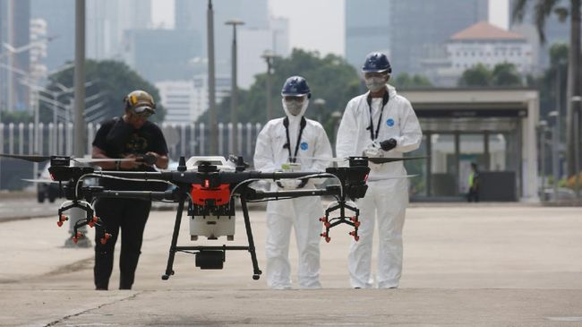 Petugas menyiapkan drone yang digunakan untuk meyemrotkan disinfektan di kawasan Jalan Jenderal Sudirman, Jakarta, Jumat (27/3/2020). Penyemprotan disinfektan tersebut dilakukan guna menekan penyebaran virus Corona (COVID-19). ANTARA FOTO/Reno Esnir/nz.