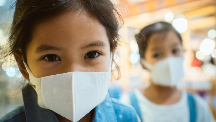 Cute asian child girl wearing protection mask to against air smog pollution with PM 2.5 in the city