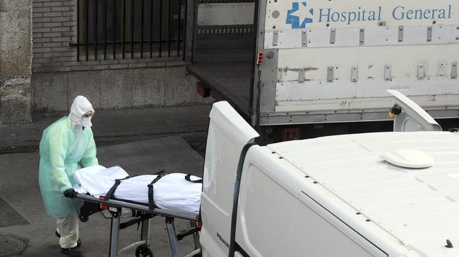 A health worker carries a body on a stretcher outside Gregorio Maranon hospital in Madrid on March 25, 2020. - Spain joined Italy today in seeing its death toll from the coronavirus epidemic surpass that of China, as more than a billion Indians joined a lockdown that has confined a third of humanity. (Photo by OSCAR DEL POZO / AFP)