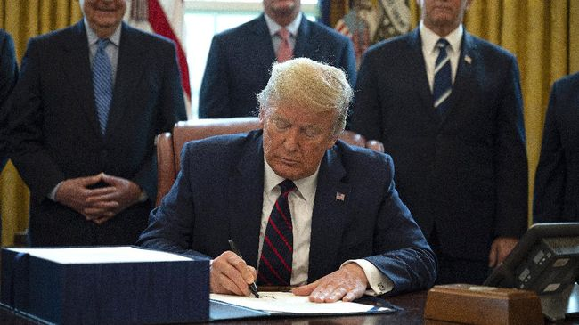 US President Donald Trump, flanked by US Senate Majority Leader Mitch McConnell (L), House Minority Leader Kevin McCarthy (C) and Vice President Mike Pence (R), signs the CARES act, a $2 trillion rescue package to provide economic relief amid the coronavirus outbreak, at the Oval Office of the White House on March 27, 2020. - After clearing the Senate earlier this week, and as the United States became the new global epicenter of the pandemic with 92,000 confirmed cases of infection, Republicans and Democrats united to greenlight the nation's largest-ever economic relief plan. (Photo by JIM WATSON / AFP)