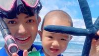 Bersama Danillo, anak semata wayangnya bermain dengan bintang laut. Pantainya pun sepi, Bun, jadi bisa menikmati pantai dengan leluasa bak pulau pribadi nih. (Foto: Instagram @bellashofie_rigan)