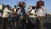Penduduk setempat memberikan makanan dan minuman bagi para buruh di India yang tengah mudik dengan berjalan kaki.(AP Photo/Altaf Qadri)