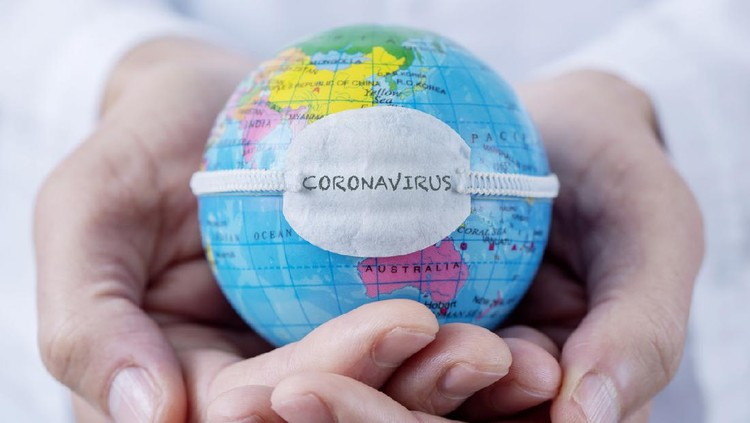 closeup of a caucasian doctor man holding a world globe with a protective mask with the word coronavirus written in it