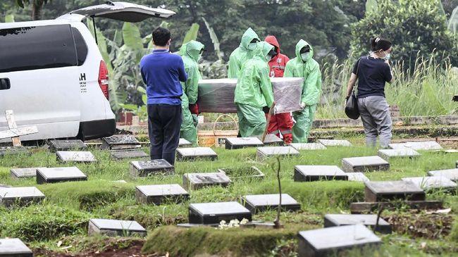 Petugas pemakaman membawa peti jenazah pasien COVID-19 di TPU Pondok Ranggon, Jakarta, Senin (30/3/2020). Juru bicara pemerintah untuk penanganan COVID-19 Achmad Yurianto per Senin (30/3/2020) pukul 12.00 WIB menyatakan jumlah pasien positif COVID-19 di Indonesia telah mencapai 1.414  kasus, pasien yang telah dinyatakan sembuh sebanyak 75 orang, sementara kasus kematian bertambah delapan orang dari sebelumnya 114 orang menjadi 122 orang. ANTARA FOTO/Muhammad Adimaja/foc.