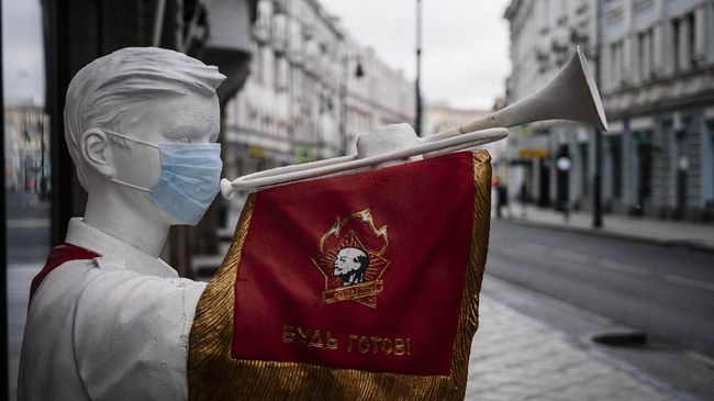 A picture shows a face mask placed on a sculpture of a Soviet pioneer playing a trumpet in front of a closed restaurant on an empty  street of downtown Moscow on March 30, 2020, as the city and its surrounding regions imposed lockdowns today, that were being followed by other Russian regions in a bid to slow the spread of the COVID-19 infection caused by the novel coronavirus. - The enforcement of the strict new rules, which Moscow Mayor suddenly announced for the capital late on March 29, coincide with the beginning of a