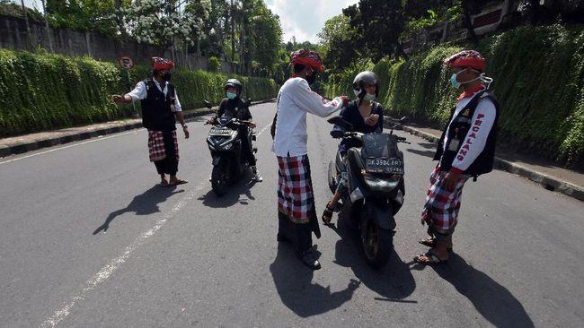 Pecalang atau petugas keamanan adat Bali memeriksa sejumlah warga yang melintas di Tabanan, Bali, Kamis (26/3/2020). Penjagaan dilakukan di setiap perbatasan desa / kota dengan melibatkan unsur pecalang, TNI dan Polri untuk mengurangi lalu lalang orang pascaimbauan gubernur Bali agar masyarakat tetap berada di rumah untuk  mencegah penyebaran COVID-19. ANTARA FOTO/Nyoman Hendra Wibowo/nym/am