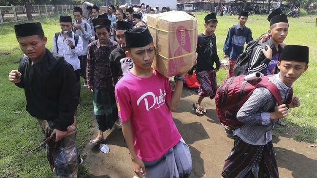 Sejumlah santri berjalan menuju bus untuk dipulangkan ke daerah asal di Pondok Pesantren (Ponpes) Lirboyo, Kota Kediri, Jawa Timur, Selasa (31/3/2020). Ponpes terbesar se-Jawa Timur tersebut memulangkan sedikitnya 22 ribu santri untuk menangkal penyebaran COVID-19. ANTARA FOTO/Prasetia Fauzani/wsj.