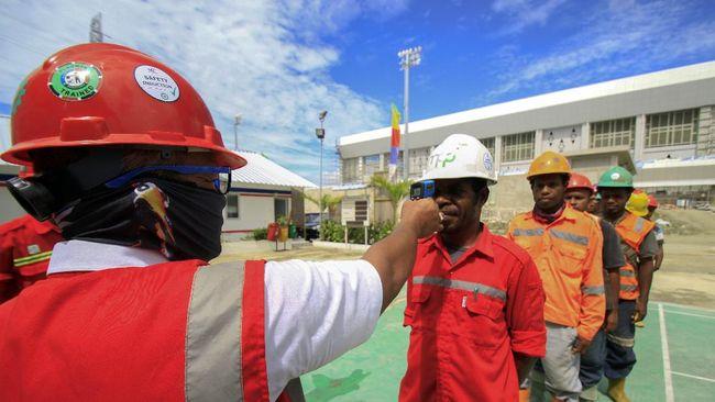Petugas mengukur suhu pekerja sebelum beraktivitas di Venue Aquatic Kampung Harapan, Sentani, Jayapura, Papua, Rabu (01/4/2020). Pemprov Papua memperpanjang pembatasan sosial hingga 13 April 2020 untuk memutus penyebaran virus corona (COVID-19) di Papua. ANTARA FOTO/Gusti Tanati/hp.