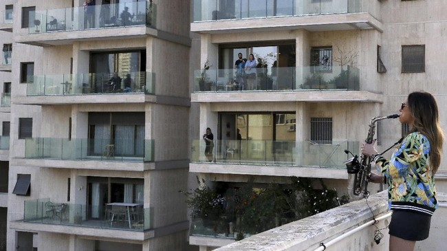 Banyak cara untuk menghadirkan kehangatan di tengah kepanikan akan virus corona. Balkon menjadi area bagi para warga untuk saling menyemangati.