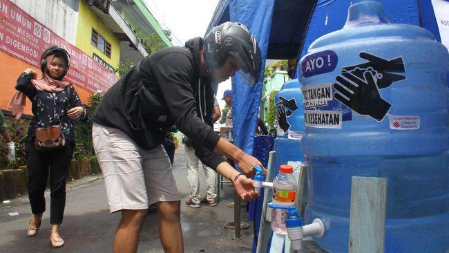 Seorang pengguna jalan mencuci tangannya sebelum masuk di Kelurahan Ketawanggede, Malang, Jawa Timur, Rabu (1/4/2020). Warga di kawasan tersebut secara swadaya melakukan screening kepada para pengguna jalan dengan menyemprotkan disinfektan, mewajibkan cuci tangan, pengukuran suhu tubuh, serta mengurangi akses jalan untuk mencegah penyebaran virus Corona. ANTARA FOTO/Ari Bowo Sucipto/hp.