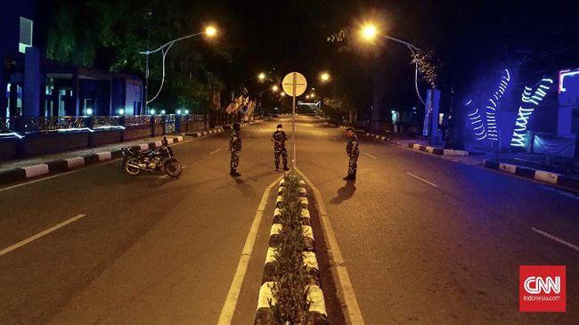 Personel TNI menjaga jalan di Banda Aceh untuk mengawasi warga yang keluyuran di malam hari.