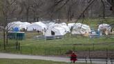 Dari kejauhan, seorang perempuan melihat anggota dan tenaga medis Dompet Samaritan tengah menyiapkan rumah sakit darurat di Centrak Park, salah satu taman kota terbesar di kota New York, Amerika Serikat. (AP Photo/Mary Altaffer)