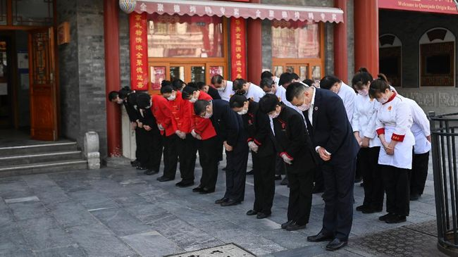 Restaurant staff members wearing face masks mourn patients and medical staff killed by coronavirus during a nationwide three minutes silence along a business street in Beijing on April 4, 2020. - China came to a standstill to mourn patients and medical staff killed by the coronavirus, with the world's most populous country observing a nationwide three-minute silence. (Photo by WANG ZHAO / AFP)