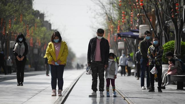 People wearing face masks mourn patients and medical staff killed by coronavirus during a nationwide three minutes silence along a business street in Beijing on April 4, 2020. - China came to a standstill to mourn patients and medical staff killed by the coronavirus, with the world's most populous country observing a nationwide three-minute silence. (Photo by WANG ZHAO / AFP)