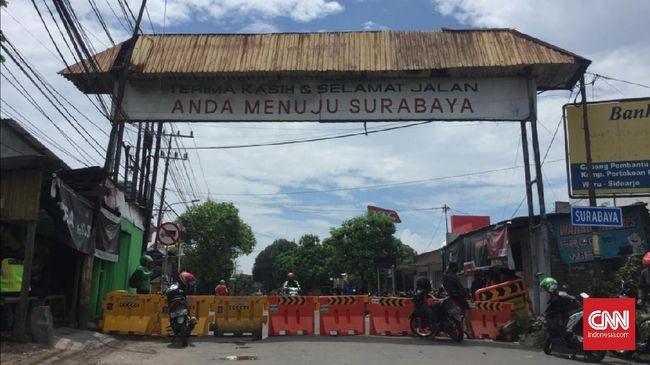 Sejumlah warga Surabaya memblokade salah satu akses jalan perbatasan Surabaya - Sidoarjo, di Jalan Raya Rungkut Menanggal Surabaya. Jalan yang ditutup tersebut berada di Perumahan Pondok Tjandra Indah, Sidoarjo.