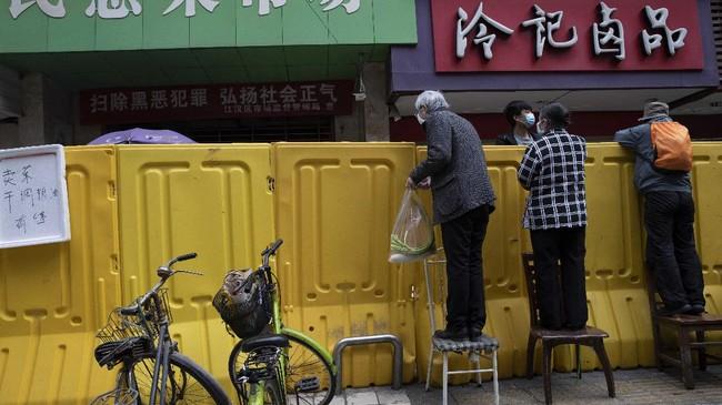 Seorang pembeli, Zan Zhongwu merasa tidak aman jika harus berbelanja ke supermarket. Namun ia mengaku cukup terbantu dengan pedagang yang tetap mengantarkan bahan makanan dari balik tembok.(AP Photo/Ng Han Guan)