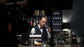 Hüggenberger berdiri di depan laptop selama sekitar dua jam dan menyajikan kepada para tamunya berbagai jenis gin. Tamu biasa, Stephan Roß, sangat menyukai pertemuan virtual. (Ina FASSBENDER/AFP)